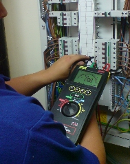 piture of electrician testing an electrcial installation with a testing instrument